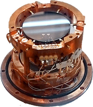 Fully assembled COSINUS detector module. Visible is the the top of the light detector which is held by screws in the copper holder. © COSINUS